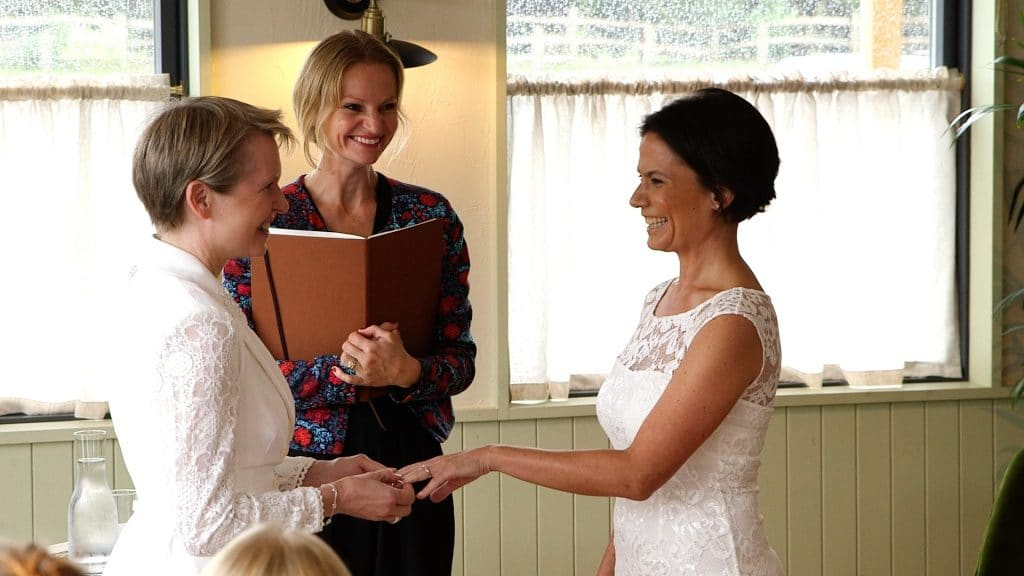 two brides and their wedding celebrant