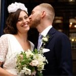groom kissing brides cheek at wedding ceremony