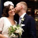 groom kissing brides cheek at wedding ceremony